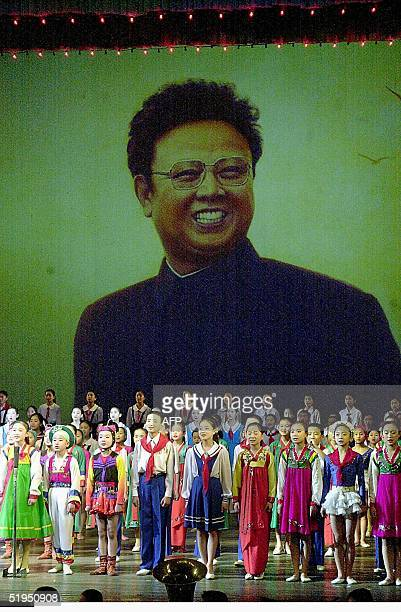 This 01 December 2000 file picture shows North Korean young boys and girls perform in front of a huge portrait of their leader Kim JongIl on a stage...