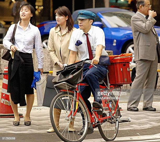 This 07 November 2003 file picture shows a Japanese postman collecting postal matters by bicycle in downtown Tokyo Japanese Prime Minister Junichiro...