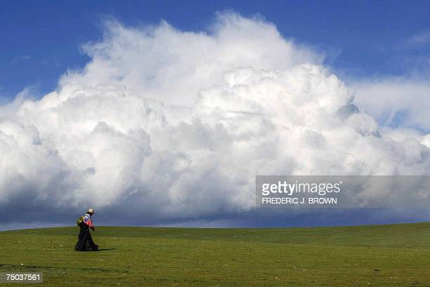 This 10 August 2002 file photo shows a seminomadic Tibetan herdswoman making her way across grasslands as hovering clouds pass on the outskirts of...