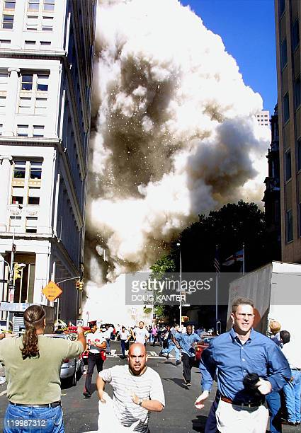 This 11 September 2001 file photo shows pedestrians running from the scene as one of the World Trade Center towers collapses in New York City...