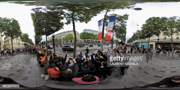 This 360 image shows supporters greeting the new French president Emmanuel Macron as he waves from his car on the Champs Elysee after the handover...