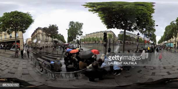 This 360 image shows supporters waiting under the rain to greet the new French president Emmanuel Macron after the handover ceremony at the Elysee...