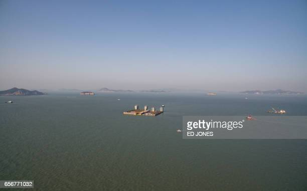 This aerial general view shows the partiallysubmerged wreck of the Sewol ferry as it is lifted between two Chinese salvage vessels off the coast of...