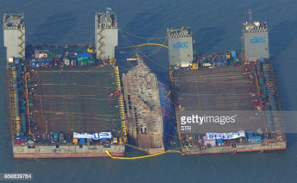 This aerial image shows part of the damaged Sewol ferry between two barges after being raised during a salvage operation at sea off the southwestern...