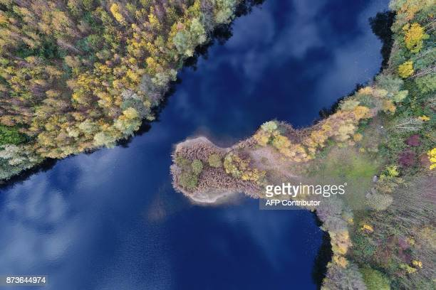 This aerial photo made using a drone shows clouds reflecting in a lake surrounded by trees in autumnal colours near Cologne western Germany on...