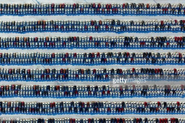 This aerial photo taken on January 16 2017 shows new cars lined up at a parking lot in Shenyang northeast China's Liaoning province Auto sales in...