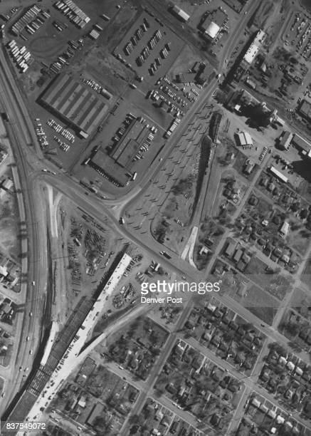 This aerial photograph looking slightly toward the southeast shows progress on the E 46th Ave freeway at Steele St where the new elevated roadway...