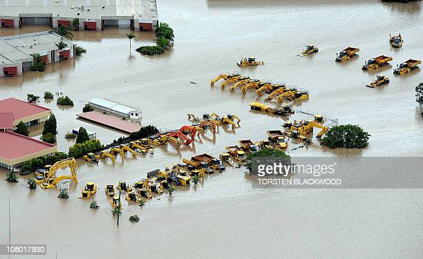 This aerial photograph shows heavy machinery used by the mining industry submerged as flood waters devastate much of Brisbane on January 13 2011...