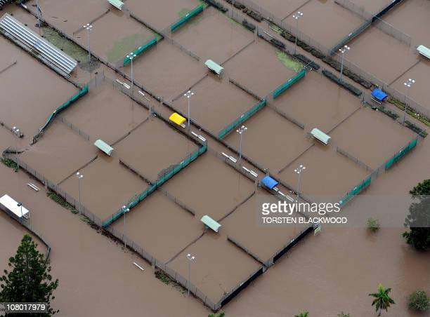 This aerial photograph shows tennis courts submerged by the Brisbane River as flood waters devastate much of Brisbane on January 13 2011 Australia's...