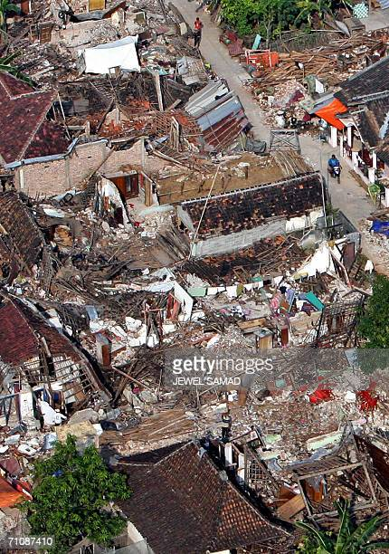 This aerial picture taken from an Indonesian Air Force helicopter en route to a relief mission shows earthquake victims waving for help standing near...
