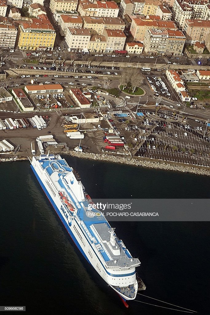 This aerial picture taken on February 13, 2016 shows the former SNCM ferry boat 'Jean Nicoli' docked at Ajaccio's port, with trucks parked in front of its boarding ramps to avoid freight loading, on the French Mediterranean island of Corsica. / AFP / Pascal POCHARD-CASABIANCA