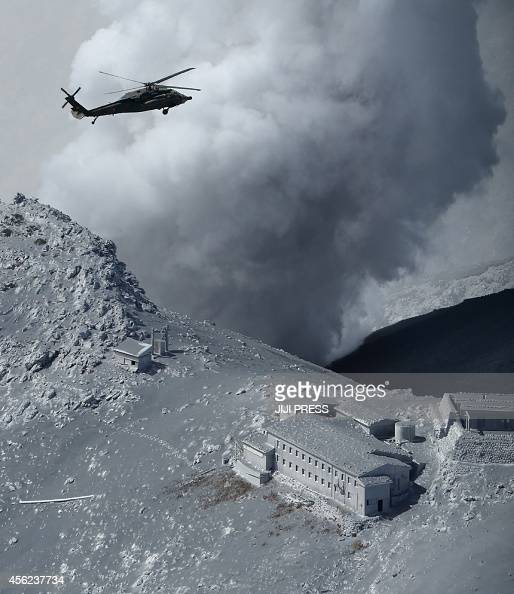 This aerial picture taken on September 28 2014 shows a helicopter of Japan's Self Defence Force hovering above a volcanic ash covered mountain...