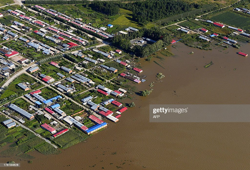 This aerial view picture taken on August 26, 2013 shows houses submerged by the flooded Heilongjiang River, called the Amur River in Russia, in Tongjiang municipality in northeastern China's Heilongjiang province. The river, which marks the border between China and Russia, has experienced its worst flooding in a century, cutting off roads to some areas, Chinese state media said on August 26. CHINA