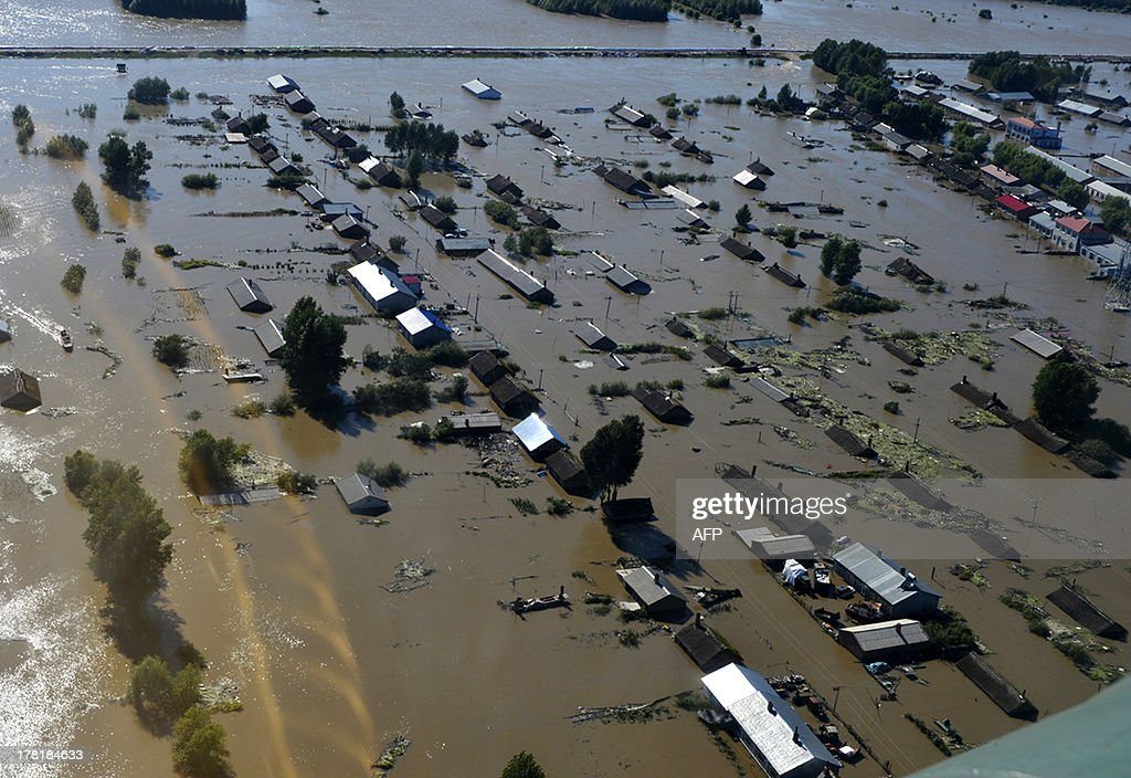 This aerial view picture taken on August 26, 2013 shows houses submerged by the flooded Heilongjiang River, called the Amur River in Russia, in Tongjiang municipality in northeastern China's Heilongjiang province. The river, which marks the border between China and Russia, has experienced its worst flooding in a century, cutting off roads to some areas, Chinese state media said on August 26. CHINA OUT AFP PHOTO