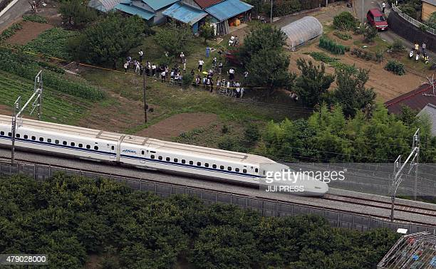 This aerial view shows a Nozomi 255 bullet train or 'shinkansen' moving slowly toward Odawara station on June 30 2015 after an apparent suicide...