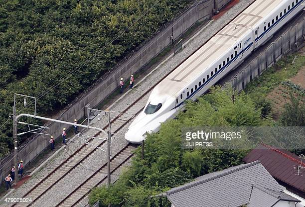 This aerial view shows a Nozomi 255 bullet train or 'shinkansen' stopping near the Odawara station on June 30 2015 after an apparent suicide attempt...