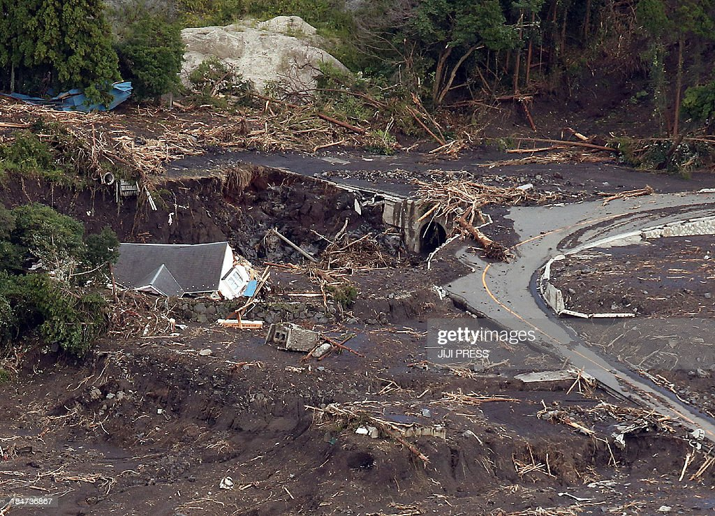 This aerial view shows houses buried by a landslide after heavy rain brought on by typhoon Wipha at Oshima island, 120km south of Tokyo on October 16, 2013. At least 13 people are known to have died after a powerful typhoon lashed Japan's Pacific coast, warning that the death toll was likely to rise.