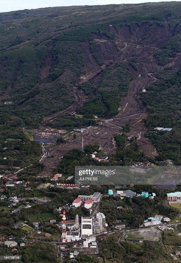This aerial view shows landslide buried houses, caused by heavy rain of typhoon Wipha at Oshima island, 120km south of Tokyo, on October 16, 2013. At least 13 people are known to have died after a powerful typhoon lashed Japan's Pacific coast, officials said, warning that the death toll was likely to rise. AFP PHOTO / JIJI PRESS JAPAN OUT
