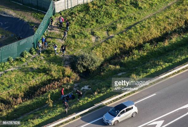This aerial view shows migrants gather on October 14 2017 by a petrol station's fence as a car drives towards the Calais ferry terminal on the A216...