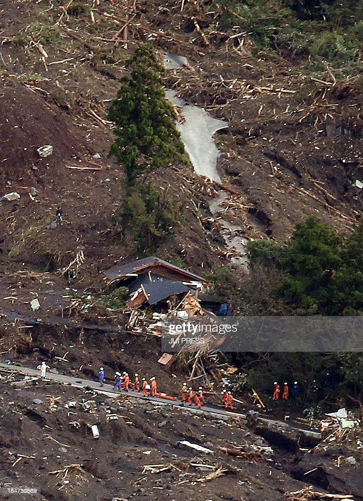 This aerial view shows rescue workers searching for survivors after a landslide buried houses following heavy rain brought on by typhoon Wipha at Oshima island, 120km south of Tokyo on October 16, 2013. At least 13 people are known to have died after a powerful typhoon lashed Japan's Pacific coast, warning that the death toll was likely to rise. AFP PHOTO / JIJI PRESS JAPAN OUT