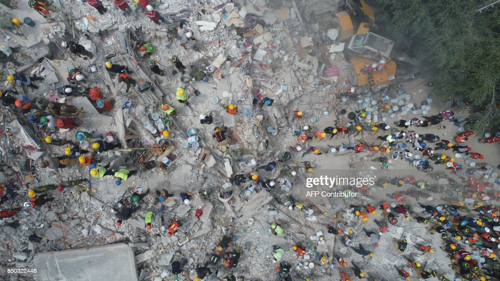 This aerial view shows rescuers, firefighters, policemen, soldiers and volunteers searching for survivors in a flattened building in Mexico City on September 20, 2017 a day after a strong quake hit central Mexico. A powerful 7.1 earthquake shook Mexico City on Tuesday, causing panic among the megalopolis' 20 million inhabitants on the 32nd anniversary of a devastating 1985 quake. / AFP PHOTO / Mario VAZQUEZ