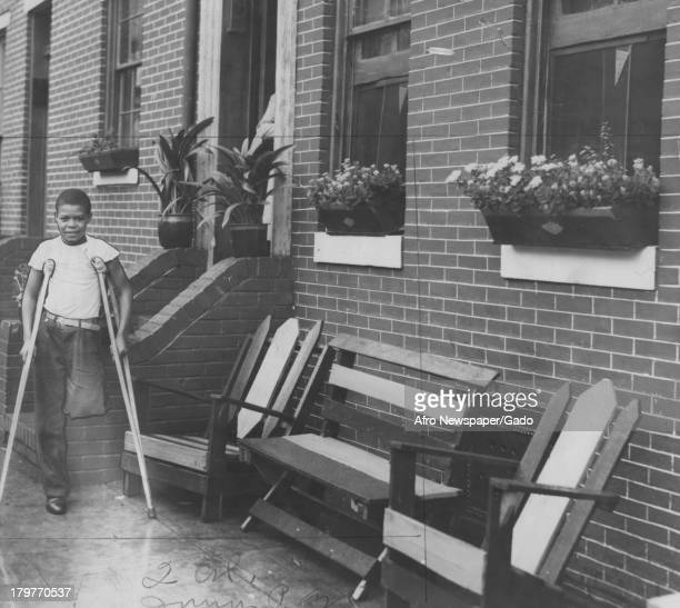 This AfricanAmerican boy is on crutches missing part of one leg Baltimore Maryland October 1938