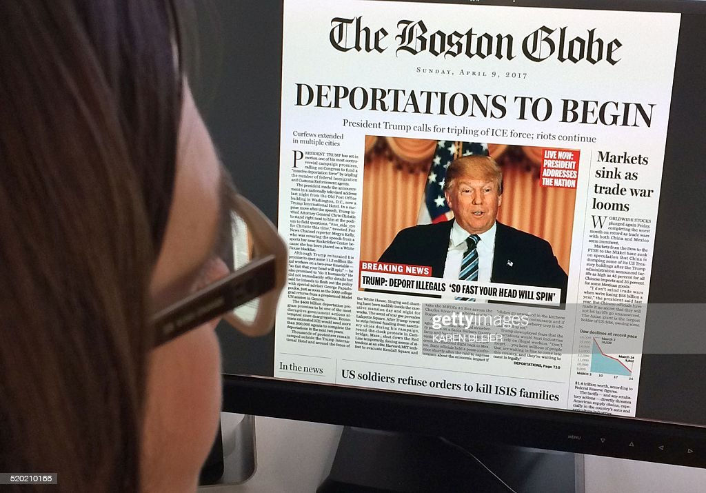 TOPSHOT - This April 10, 2016 photo taken in Washington shows a woman reading an online version of a mockup of what a frontpage might look like should Republican frontrunner Donald Trump win the presidency, as it condemned his 'deeply disturbing' and 'profoundly un-American' vision. 'Deportations to begin, President Trump calls for tripling of ICE (immigration and customs enforcement); riots continue,' read The Boston Globe's fake headline, dated April 9, 2017. It was posted on the editorial page, accompanied by a ruthless editorial article saying Trump's campaign 'demands an active and engaged opposition.' / AFP / Karen BLEIER