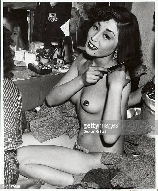 This attractive Japanese burlesque girl displays the sparkle in her eyes as she posese at her dressing table in a Tokyo burlesque theatre The girls...