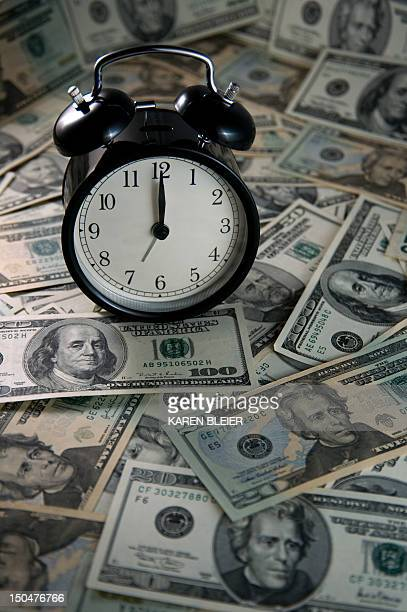 This August 18 2012 photo illustration shows an alarm clock and US currency AFP PHOTO/Karen BLEIER