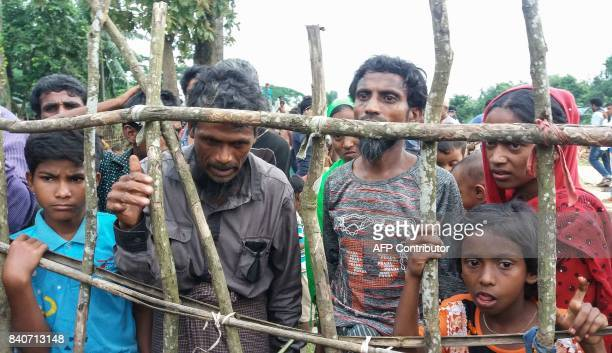 This August 29 2017 photo shows newly arrived Rohingya refugees standing behind a wooden fence at Kutupalong refugee camp in Ukhiya after crossing...