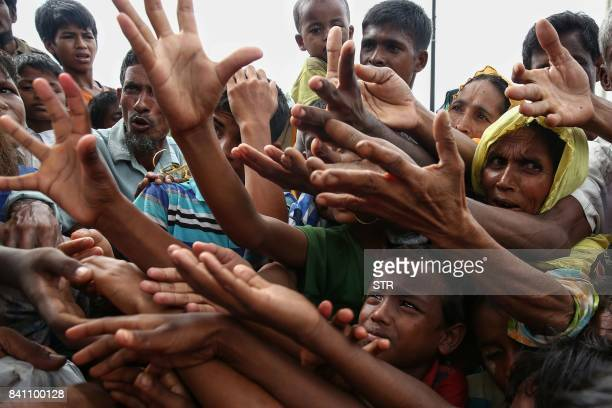 TOPSHOT This August 30 2017 photo shows Rohingya refugees reaching for food aid at Kutupalong refugee camp in Ukhiya near the BangladeshMyanmar...