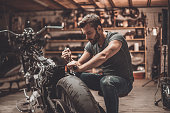 Confident young man repairing motorcycle in repair shop