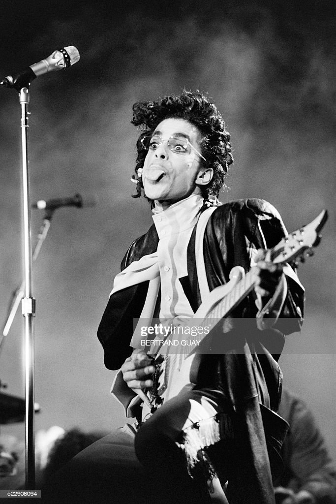 This black and white photo taken on June 15 1987 shows musician Prince performing on stage during his concert at the Bercy venue in Paris Pop icon...