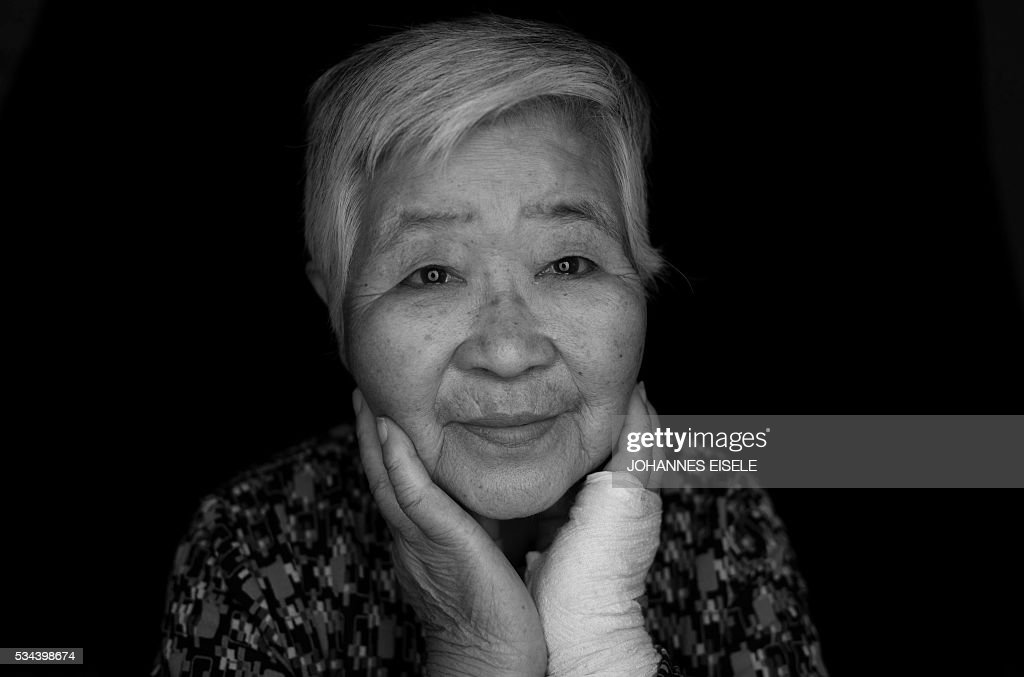 This black and white picture taken on May 26, 2016 shows Misako Katani, 86, who was exposed to radiation in Hiroshima and Nagasaki, posing for a picture in a nursery home in Hiroshima Prefecture. Katani, who survived the Hiroshima blast August 6, 1945, was then again exposed to radiation in Nagasaki shortly after that city was bombed on August 9. US President Barack Obama is set to become the first sitting US president to visit one of the bomb sites when he journeys on May 27, 2016 with Japanese Prime Minister Shinzo Abe to Hiroshima, hallowed ground to Japanese but, for more than 70 years, a no-go zone for 11 of his Oval Office predecessors. / AFP / JOHANNES