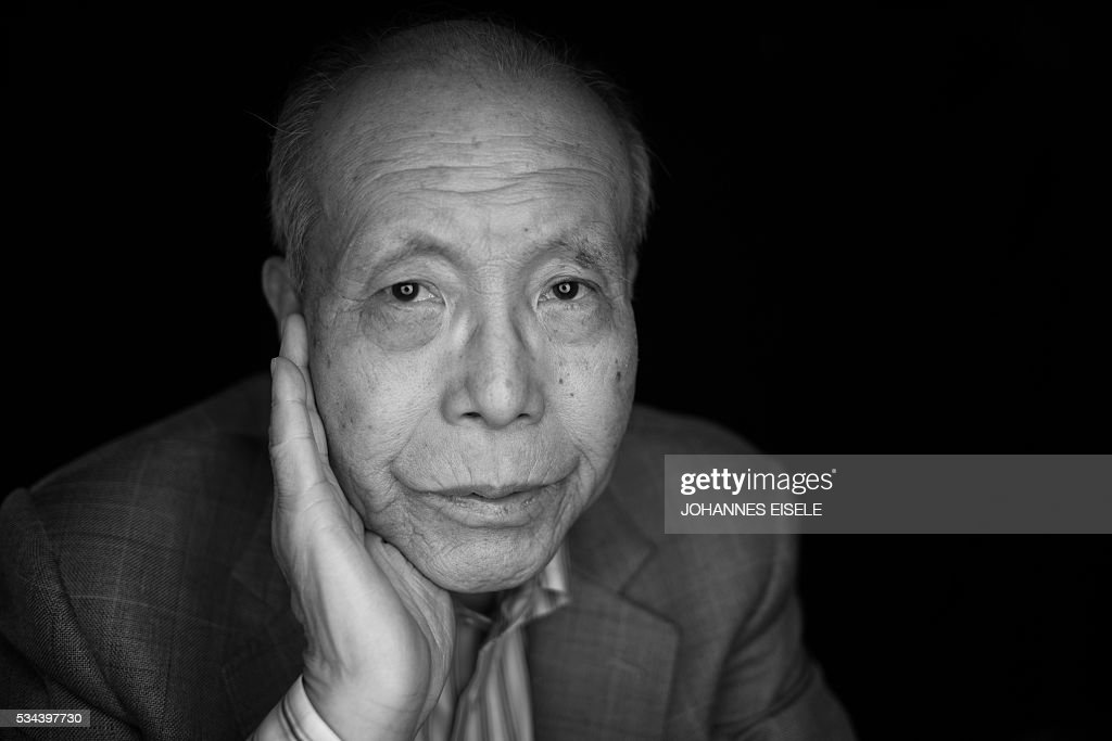 This black and white picture taken on May 26, 2016 shows Shigeaki Mori, a survivor of the atomic bombing of Hiroshima and a historian, posing for a picture at his home in Hiroshima. The atomic blast at Hiroshima on August 6, 1945 killed 140,000 people, half of whom died quickly from intense heat, a huge shock wave, and radiation. US President Barack Obama is set to become the first sitting US president to visit one of the bomb sites when he journeys on May 27, 2016 with Japanese Prime Minister Shinzo Abe to Hiroshima, hallowed ground to Japanese but, for more than 70 years, a no-go zone for 11 of his Oval Office predecessors. / AFP / JOHANNES