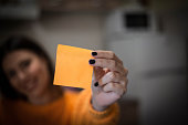 Woman holding yellow paper,close up.