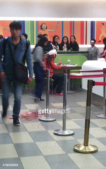 This cellphone photo taken on March 2 2014 shows an injured woman sitting in a restaurant in the Kunming railway station after an attack in Kunming...