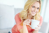 Cropped view of a beautiful blonde woman smiling while relaxing at home and drinking coffee