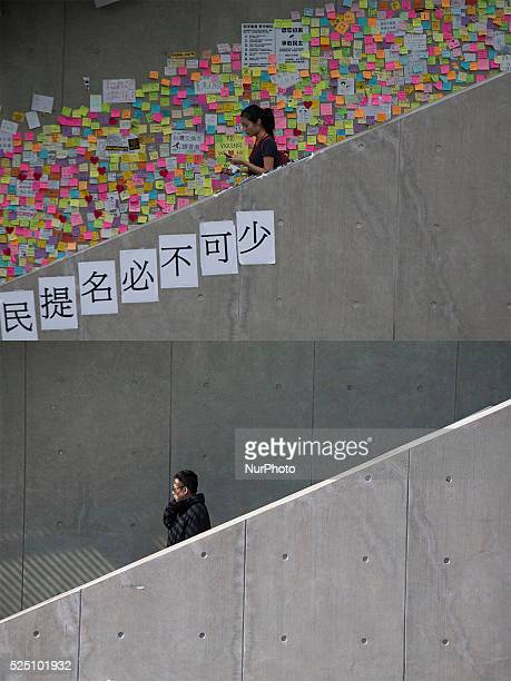 This combo shows on the top a picture taken on Oct 5 2014 a woman walks past a wall covered by postit messages made by protester and on the bottom a...