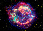 Infrared data from the Spitzer Space Telescope are colored red; visible data from the Hubble Space Telescope are yellow; and X-ray data from the Chandra X-ray Observatory are green and blue.  Located