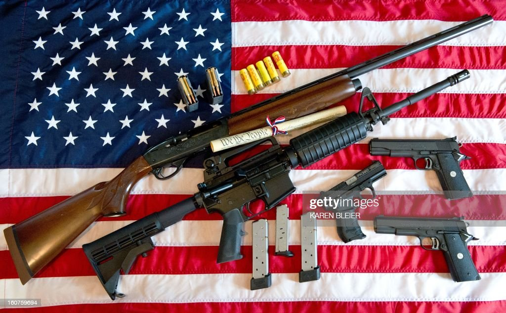 This February 4, 2013 photo illustration in Manassas, Virginia, shows a Remington 20-gauge semi-automatic shotgun, a Colt AR-15 semi-automatic rifle, a Colt .45 semi-auto handgun, a Walther PK380 semi-auto handgun and various ammunition clips with a copy of the US Constitution on top of the American flag. US President Barack Obama Monday heaped pressure on Congress for action 'soon' on curbing gun violence. Obama made a pragmatic case for legislation on the contentious issue, arguing that just because political leaders could not save every life, they should at least try to save some victims of rampant gun crime. AFP PHOTO/Karen BLEIER