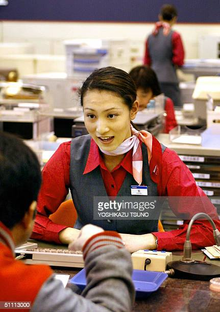 This file photo dated 01 April 2002 shows a female teller of Mizuho Bank receiving one of the first customers at the new 'mega' bank which has a...