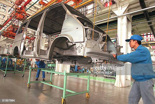 This file photo dated 02 December 1997 shows workers at the FordJiangling China Transit factory lowering the body frame of one of the jointlydesigned...