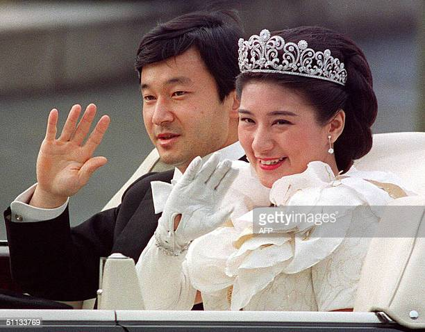 This file photo dated 09 June 1993 shows Japanese Crown Prince Naruhito and Crown Princess Masako waving to people during the parade after their...
