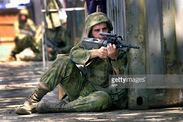 This file photo dated 23 September 1999 shows Australian soldiers taking positions behind shipping containers at the Dili port after shots were fired...