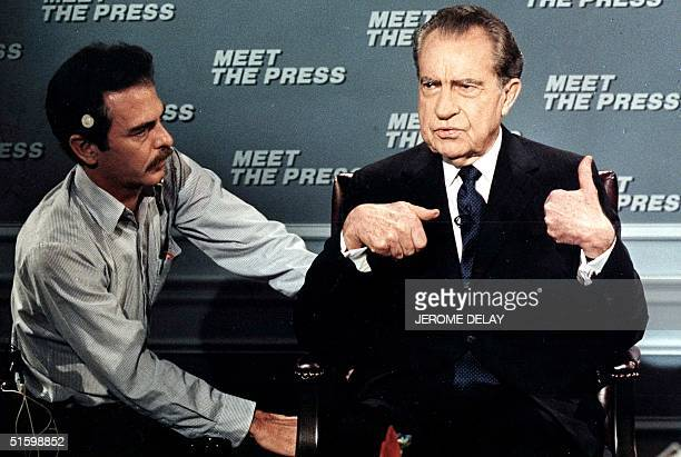 This file photo shows former US President Richard Nixon as he gestures while being wired for a microphone by an NBC technician 09 April 1988 in...