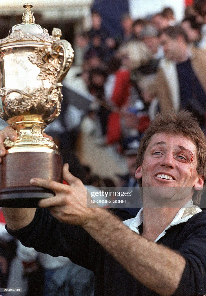 This file photo taken 20 June 1987 shows thenAll Black captain David Kirk holding up the 'William Webb Ellis' trophy after New Zealand's victory in...