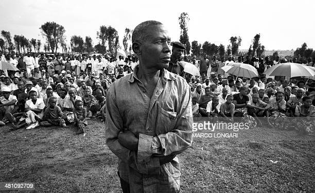 This file photo taken October 16 2001 in Runda shows a Rwandan inmate standing looking away while residents gather on a hillside field to attend a...