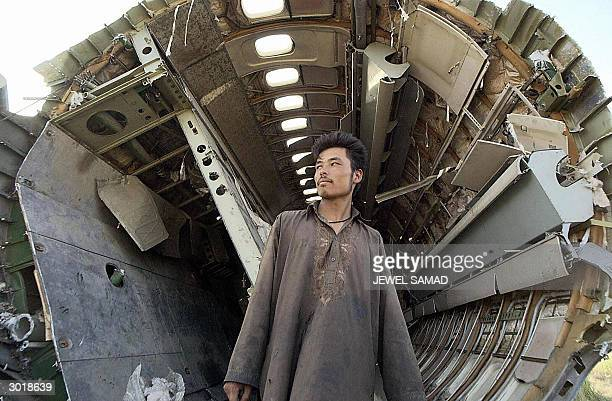 This file picture taken 06 July 2002 shows an Afghan worker coming out of a destroyed Afghan national airlines plane Ariana Afghan Airlines after...