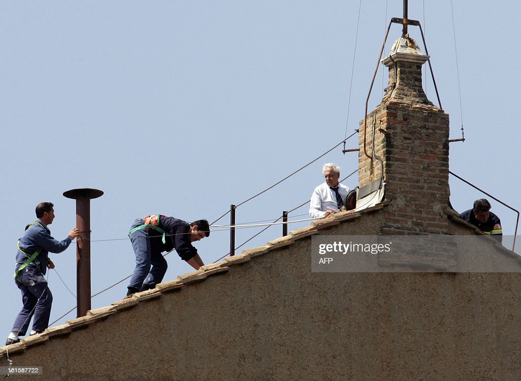 This file picture taken on April 15, 2005 shows Vatican workers place the chimney pot on the roof of the Sistine Chapel for the conclave starting 18 April 2005. The Catholic Church faced a tricky transition on February 12, 2013 as it prepared to elect a new pope, with many faithful still reeling from the shock resignation of Pope Benedict XVI. AFP PHOTO/ FILES / Patrick HERTZOG